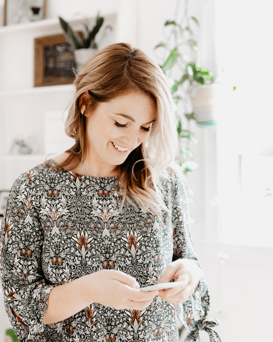woman looking down and laughing at her iphone wearing patterned dress